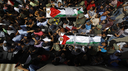Mourners carry the bodies of two Palestinians, who were shot dead by Israeli forces on Thursday, during their funeral in the West Bank city of Ramallah May 16, 2014. (Reuters / Mohamad Torokman)