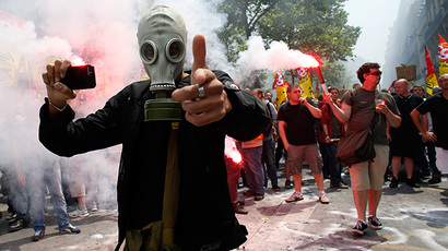 A protester wearing a gas mask holds a smartphone and gestures during a demonstration by striking employees of the French state rail company SNCF near the Transport Ministry in Paris on June 12, 2014, on the second day of a nation-wide strike to protest a government railway reform project. (AFP Photo / Bertrand Guay)