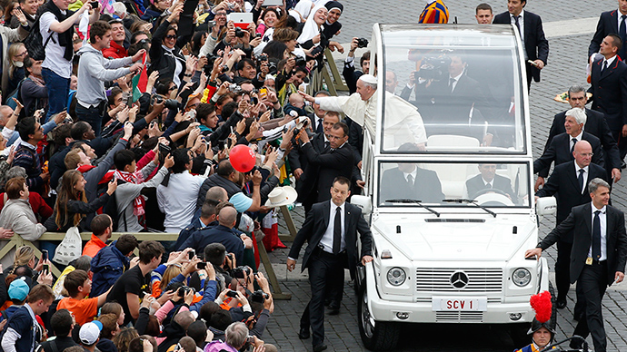 Pope Francis greets the faithful as he rides in his Popemobile after the canonisation ceremony of Popes John XXIII and John Paul II in St Peter's Square at the Vatican, April 27, 2014 (Reuters / Stefano Rellandini)