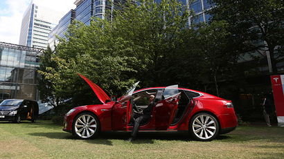 A visitor looks at a Tesla Model S electric car at the Motorexpo in Canary Wharf, London, June 13, 2014 (Reuters / Marika Kochiashvili)