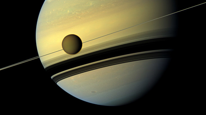 Titan, Saturn's largest moon appears before the planet as it undergoes seasonal changes in this natural color view from NASA's Cassini spacecraft in this handout released by NASA August 29, 2012. (Reuters/NASA)