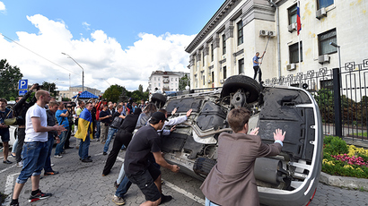 People flip a car over during a rally against the Russian president in front of the Russian embassy in Kiev on June 14, 2014 (AFP Photo / Sergey Supinsky)