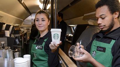 US coffee giant Starbucks employee Essia (L) and Egole prepare beverages. (AFP Photo / Fabrice Coffrini)