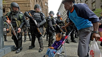 A resident and child pass riot police as they patrol a street during a demonstration against the G20 summit in downtown Pittsburgh, Pennsylvania. (AFP Photo / Paul J. Richards)