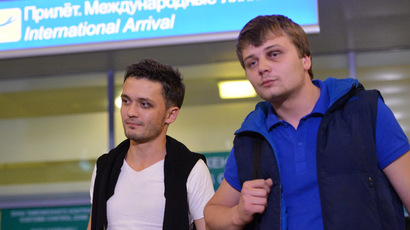 Zvezda TV channel correspondent Evgeny Davydov, left, and sound engineer Nikita Konashenkov who were detained in Dnepropetrovsk are welcomed on their arrival at Moscow's Sheremetyevo airport after the release. (RIA Novosti/Alexey Kudenko)
