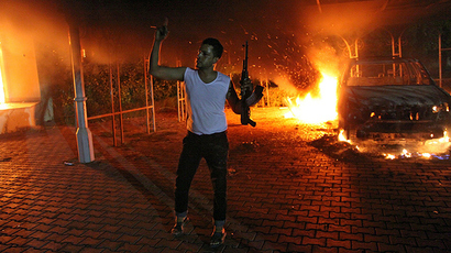 ARCHIVE PHOTO: A file picture taken on September 11, 2012 shows an armed man waving his rifle as buildings and cars are engulfed in flames after being set on fire inside the US consulate compound in Benghazi (AFP Photo / STR)