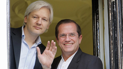WikiLeaks founder Julian Assange waves from a window with Ecuador's Foreign Affairs Minister Ricardo Patino (R) at Ecuador's embassy in central London June 16, 2013. (Reuters/Chris Helgren)