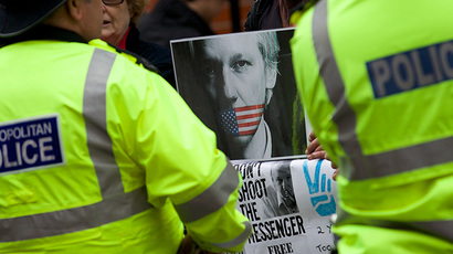 Police stand guard in front of supporters of WikiLeaks founder Julian Assange who are standing with banners outside the Ecuadorian Embassy in London on June 19, 2014 where Julian Assange has taken refuge for two years. (AFP Photo / Andrew Cowie)