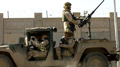 US soldiers from the 1st Battalion, 22nd Regiment of the 4th Infantry Division, ride on a military vehicle as they leave their base on a mission in Tikrit, 180 Kilometers north of Iraqi capital Baghdad, 30 December 2003. (AFP Photo / Jewel Samad)