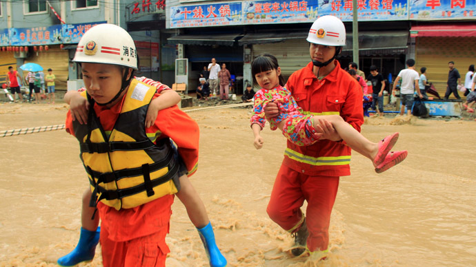 This picture taken on June 4, 2014 shows rescuers helping two children cross a heavily flooded street in Shiqian county of Tongren, southwest China's Guizhou province (AFP Photo)