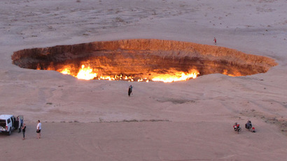 "A picture taken on May 3, 2014, shows people visiting ""The Gateway to Hell,"" a huge burning gas crater in the heart of Turkmenistan's Karakum desert.  (AFP Photo/Igor Sasin)"