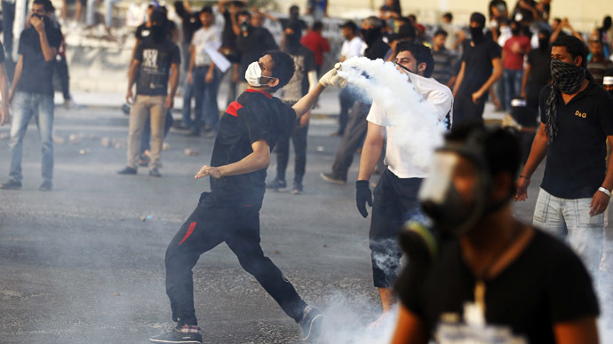 An anti-government protester throws back a tear-gas canister that was fired by the police as they clash during a funeral procession for fellow protester Sayed Mohsen, in the village of Sitra south of Manama, May 27, 2014. (Reuters/Hamad I Mohammed)