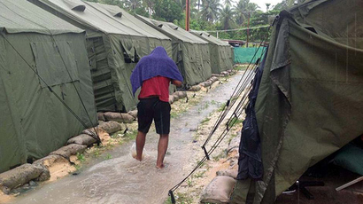 A man walking between tents at Australia's regional processing centre on Manus Island in Papua New Guinea (AFP Photo)