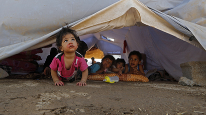 Displaced Iraqi children sit inside a UNHCR tent at a temporary camp set up to shelter people fleeing violence in northern Iraq on June 17, 2014 in Aski kalak, 40 kms west of the Kurdish autonomous region's capital Arbil (AFP Photo / Karim Sahib)