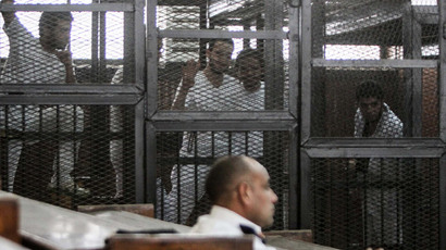 Defendents who are in custody stand in the accused cells during the trial of 20 individuals, including five Al-Jazeera journalists, for allegedly defaming the country and ties to the blacklisted Muslim Brotherhood in the police institute near Cairo's Turah prison. (AFP Photo / Mohamed El-ShahedD)