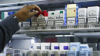A shopkeeper reaches for a packet of cigarettes in a newsagent in London (Reuters / Suzanne Plunkett)