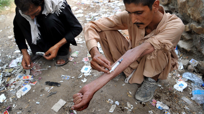 An Afghan addict smokes heroin while another addict injects heroin in the city of Jalalabad (AFP Photo / Noorullah Shirzada)