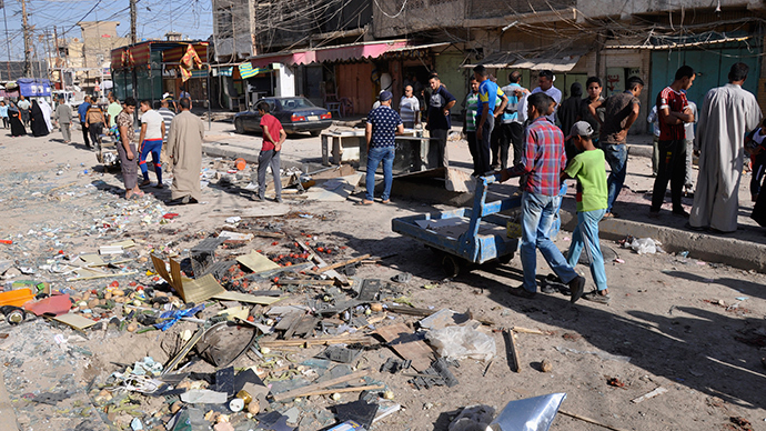 Residents look at the site of a suicide bomber attack in Mahmoudiya, south of Baghdad June 26, 2014 (Reuters / Ibrahim Sultan)