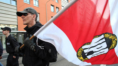 A neo-Nazi protester of Germany's extreme right NPD party carries a flag during a demonstration in Frankfurt (AFP Photo / Thomas Lohnes)