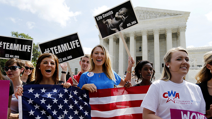 Anti-abortion protestors celebrate the U.S. Supreme Court's ruling striking down a Massachusetts law that mandated a protective buffer zone around abortion clinics, as the demonstrators stand outside the Court  in Washington June 26, 2014. (Reuters / Jim Bourg)