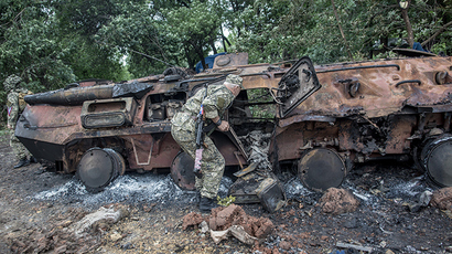 A self-defense member inspects a burnt Ukrainian armored personnel carrier near Slavyansk on June 27, 2014. (RIA Novosti / Andrey Stenin)