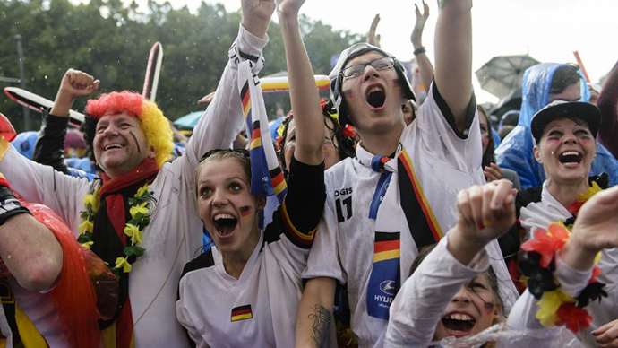 German fans celebrate while they watch the FIFA World Cup 2014 group G football match Germany vs USA in the rain on a giant screen in Berlin, Germany on June 26, 2014. (AFP Photo / Clemens Bilan)