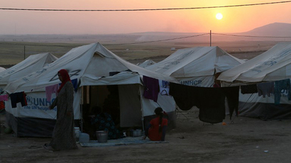 An Iraqi displaced woman walks at sunset past a tent provided by the UN refugee agency at a temporary camp set up to shelter people fleeing violence in northern Iraq on June 27, 2014 in Aski kalak, 40 kms west of the Kurdish autonomous region's capital Arbil. (AFP Photo / Karim Sahib)