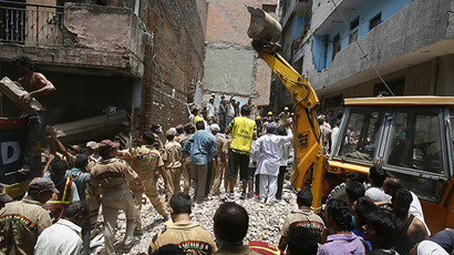 Rescue workers and volunteers stand at the site of a collapsed building in New Delhi June 28, 2014. (Reuters / Anindito Mukherjee)