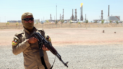 A member of Kurdish security forces takes up position with his weapon as he guards an oil refinery on the outskirts of Mosul, June 22, 2014 (Reuters / Azad Lashkari)