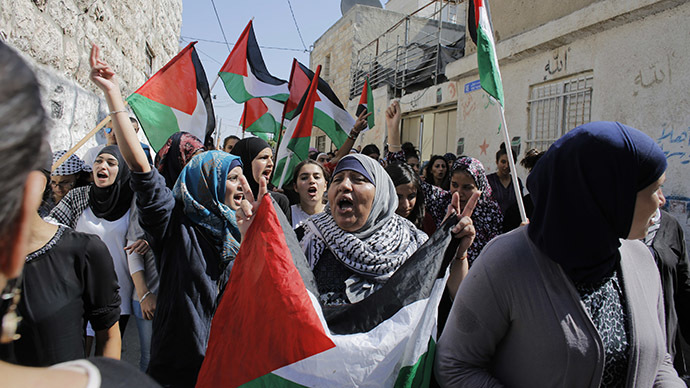Palestinian women hold flags as they chant slogans during the funeral of 16-year-old Mohammed Abu Khudair in Shuafat, an Arab suburb of Jerusalem, July 4, 2014. (Reuters / Ammar Awad)