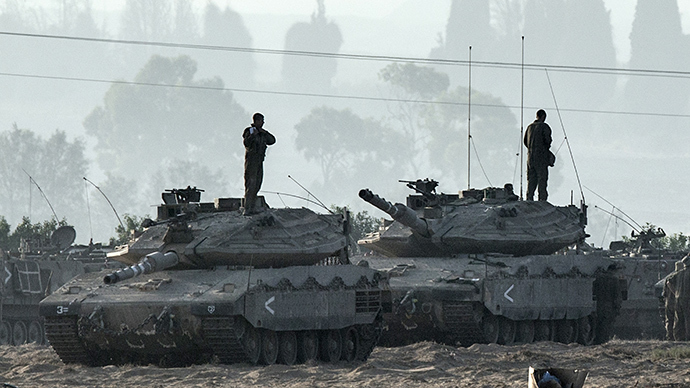 Israeli soldiers stand on Merkava tanks in an army deployment area near Israel's border with the Gaza Strip on July 8, 2014 (AFP Photo / Jack Guez)