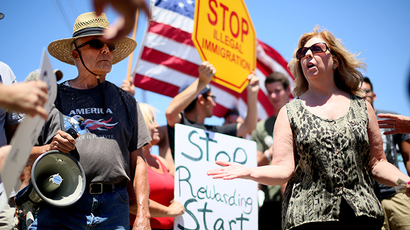 Immigrant rights activist Mary Estrada (R) speaks with anti-immigration activists during a protest outside of the U.S. Border Patrol Murrieta Station on July 7, 2014 in Murrieta, California (Reuters / Sandy Huffaker)