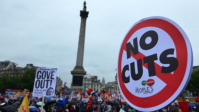 People hold banners and placards as they take part in a march and rally in central London on July 10, 2014, as more than one million public sector workers went on strike in Britain over pay and spending cuts by the government imposed as part of its austerity programme, trade unions said (AFP Photo / Carl Court)