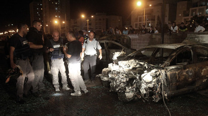 Israeli polce bomb technicians stand by a car damaged by a rocket fired from the Gaza strip, hitting the city of Ashdod on July 10, 2014.(AFP Photo / David Buimovitch )