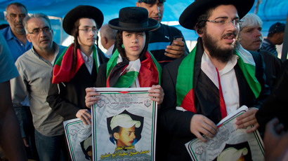 Members of Neturei Karta, a small faction of anti-Zionist ultra-Orthodox Jews who oppose Israel's existence, hold pictures of Palestinian youth Mohammed Abu Khder.(AFP Photo / Ahmad Gharabli)