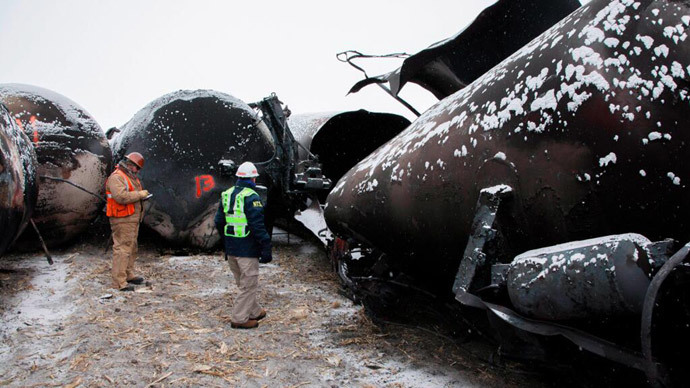 National Transporation and Safety Board (NTSB) member Robert Sumwalt (R) views damaged rail cars at the scene of the BNSF train accident in Casselton, North Dakota January 1, 2014 in this handout provided by NTSB.(Reuters / NTSB)