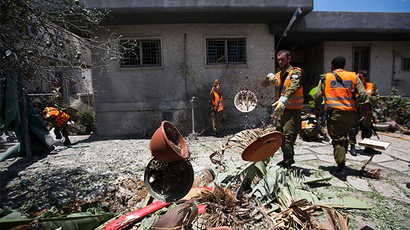 Israeli soldiers clear debris at the scene after a rocket fired by Palestinian militants in Gaza landed in Ashdod July 15, 2014 (Reuters / Amir Cohen)