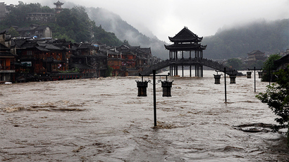 Street lamps are seen among floodwaters next to partially submerged buildings by an over flowing river at the ancient town as heavy rainfall hits Fenghuang county, Hunan province July 15, 2014 (Reuters / China Daily)