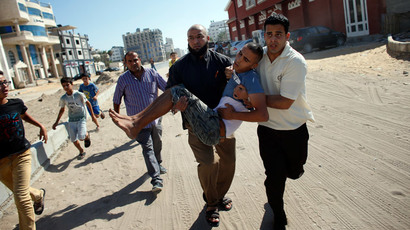 Palestinian employees of Gaza City's al-Deira hotel carry a wounded boy following an Israeli military strike nearby on the beach, on July 16, 2014.(AFP Photo / Thomas Coex )