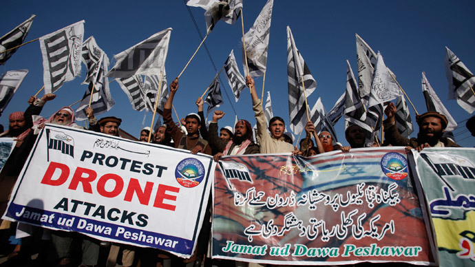 Supporters of the Jamaat-ud-Dawa Islamic organization hold placards and party flags as they shout slogans during a protest against U.S. drone attacks in the Pakistani tribal region, in Peshawar November 29, 2013.(Reuters / Fayaz Aziz)