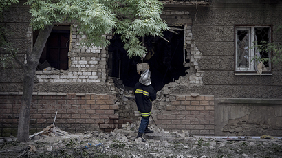 A firefighter examones the facade of a residential house damaged in artillery shelling of Lugansk 18 July, 2014 (RIA Novosti / Valery Melnikov)