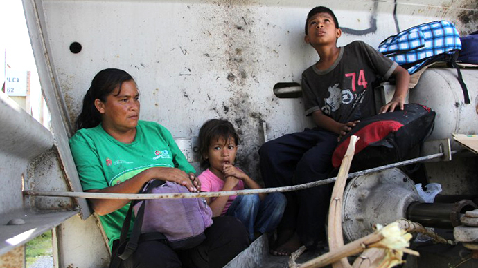 A Central American immigrant and her children sit inside the so-called La Bestia (The Beast) cargo train, in an attempt to reach the Mexico-US border, in Arriaga, Chiapas state, Mexico on July 16, 2014. (AFP Photo / Elizabeth Ruiz)