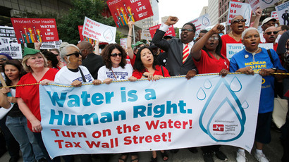 People hold a banner against the mass water shut-offs to Detroit citizens behind in their payments, during a protest in downtown Detroit, Michigan July 18, 2014.(Reuters / Rebecca Cook)