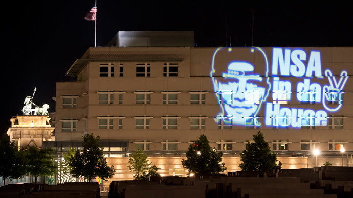 "The facade of the US embassy is illuminated with a light installation by German artist Oliver Bienkowski showing an image of US President Barack Obama wearing a baseball cap and reading ""NSA in da House"" in Berlin on early July 19, 2014.(AFP Photo / Soeren Stache)"