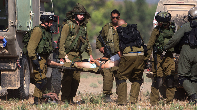 An injured Israeli soldier is evacuated from near the Israeli border with Gaza Strip on July 21, 2014, following heavy fights between Israeli soldiers to Palestinian militants. (AFP Photo / Menahem Kahana)