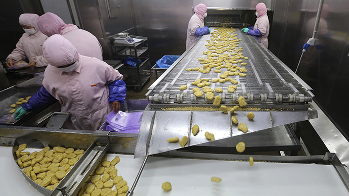 Employees work at a production line prior to a seizure conducted by officers from the Shanghai Food and Drug Administration, at the Husi Food factory in Shanghai, July 20, 2014. (Reuters)