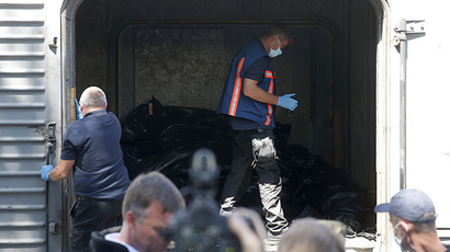 Monitors from the Organization for Security and Cooperation in Europe (OSCE) and members of a forensic team inspect a refrigerator wagon, containing the remains of victims from the downed Malaysia Airlines Flight MH17, at a railway station in the eastern Ukrainian town of Torez July 21, 2014. (Reuters / Maxim Zmeyev)