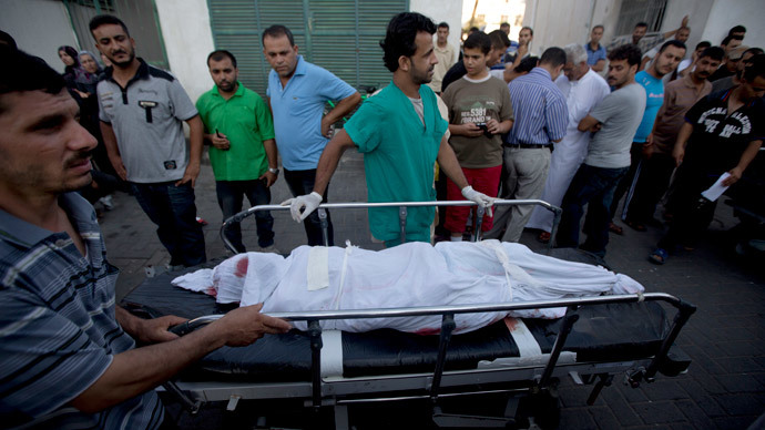 Palestinians push a stretcher carrying the body of a member of the al-Qasas family who was killed in an Israeli army shelling on July 21, 2014, as they arrive at the morgue of the al-Shifa hospital in Gaza city.  (AFP Photo / Mahmud Hams)