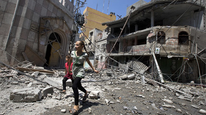 Palestinian girls walk amidst debris following an Israeli military strike in Gaza city, on July 23, 2014. (AFP Photo/MAHMUD HAMS)