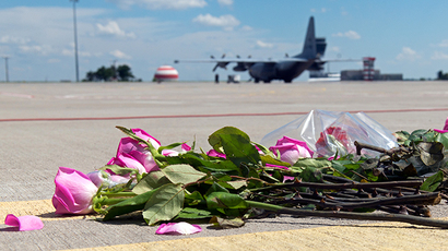 Flowers lay on the tarmac as a ground Hercules transport aircraft of the Royal Dutch Airforce, carrying bodies from downed Malaysia Airlines flight MH17 prepares to take off from Kharkiv airport on July 23, 2014. (AFP Photo / Sergei Bobok)